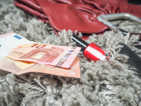 Two ten euro notes lying next to a red female handbag