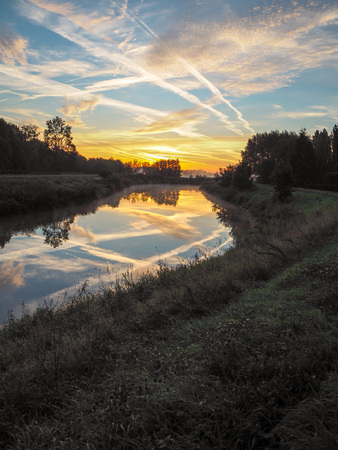 Vibrant reflection of the sun and blue sky in the river Dyle in Muizen, Belgium, during sunrise in the month September