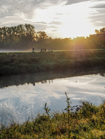 Misty morning landscape at the Dijle river and Mechelen Marsh nature park with an idyllic bench in Muizen, Belgium Stockfoto