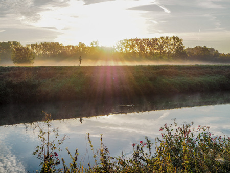 Person going for a run along the Dijle river in Muizen during a beautiful misty sunrise Stockfoto