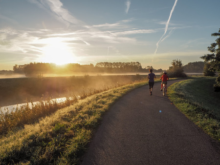 Cycling young son accompanying his jogging mother on a early misty morning run during sunrise. Mechelen, Belgium Stockfoto