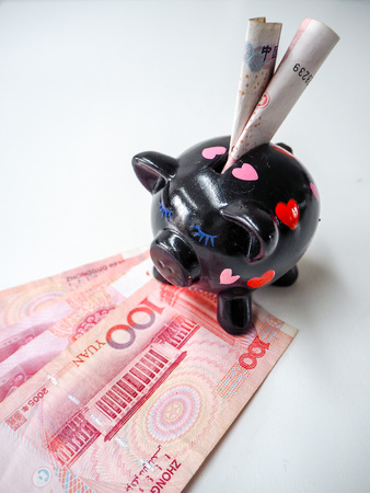 Black piggy bank standing next to Chinese 100 rmb banknotes on a white wooden background. The pig symbols fortune in the Chinese zodiac.