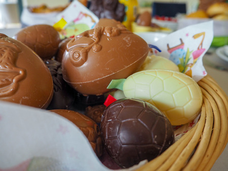 Variety of white, brown and dark chocolate easter eggs in a wicker basket for an easter brunch