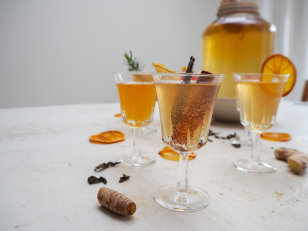 Multiple glasses with a variety of flavored kombucha tea such as cinnamon, citrus, turmeric and rosemary on a white background Imagens