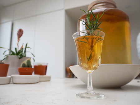 Glass with fresh homemade flavored kombucha tea on a counter top in a white kitchen