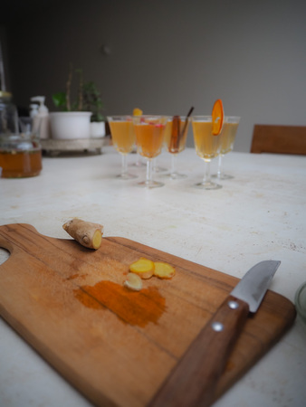 Wooden cutting board with fresh turmeric and a knife on a white table top with flutes glasses filled with kombucha tea