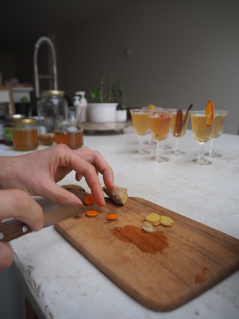 Woman cutting fresh turmeric on a wooden cutting board on a white table top with flutes glasses filled with kombucha tea