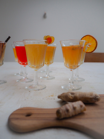 Multiple glasses with a variety of flavored kombucha tea such as citrus, cinnamon, raspberry and a wooden cutting board with turmeric Imagens