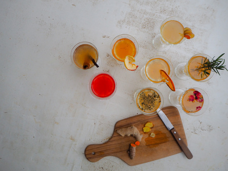 Multiple glasses with a variety of flavored kombucha such as cinnamon, turmeric, ginger, raspberry and a wooden cutting board on a white background Imagens