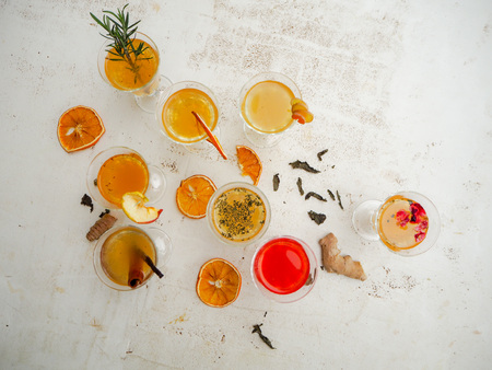 Multiple glasses with a variety of kombucha flavors such as raspberry, ginger, citrus, cinnamon, apple,rose peddles and rosemary on a white background Imagens