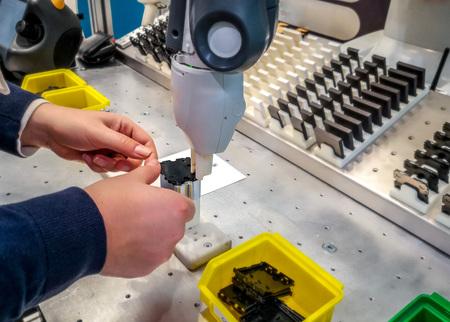 Operadora caucásica de pie en una estación de trabajo de ensamblaje con un robot colaborativo o cobot Foto de archivo