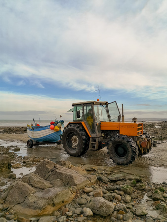 December 2018 - Wissant, France: Orange tractor towing a wooden white and blue fishing boat on a rocky beach during low tide Standard-Bild - 121304981