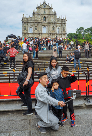 November 2018 - Macau, China: Asian man taking a family selfie in front of the Ruins of St. Pauls in a large mass of Chinese tourists