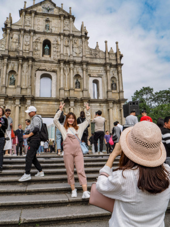November 2018 - Macau, China; Young Asian woman taking a picture of a posing friend in front of the Ruins of St. Pauls Cathedral