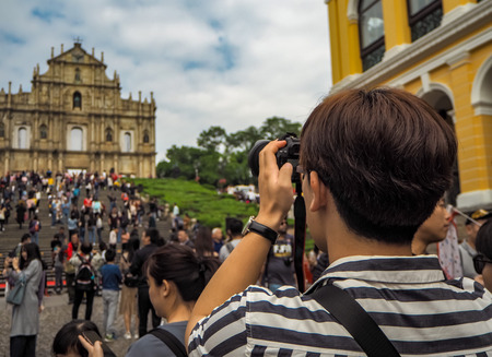 November 2018 - Macao, China: Young Asian man using a camera to take a picture of the Ruins of St. Pauls in a large mass of Chinese tourists
