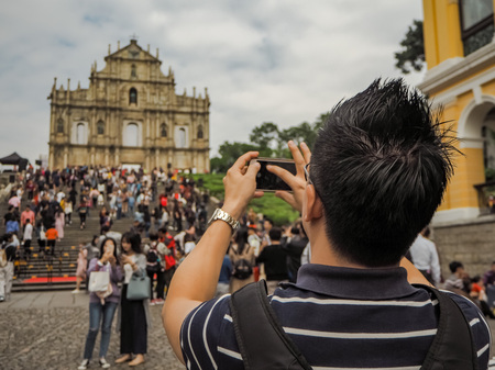 November 2018 - Macao, China: Young Asian man using a smartphone to take a picture of the Ruins of St. Pauls in a large mass of Chinese tourists