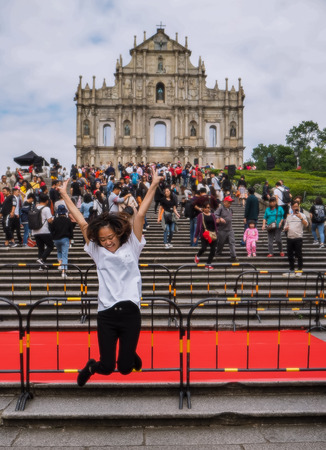 November 2018 - Macao, China: Young Asian woman posing for a jumping picture in front of the ruins of St. Paul's in a large mass of Chinese tourists Stock fotó - 127150450