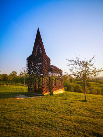 Steel see-through church in Borgloon (Hesbaye, Belgium), known as the art project Reading between the lines, during sunset