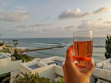 Woman holding a glass of ros? sparkling wine in a glass overlooking the coast of Cyprus