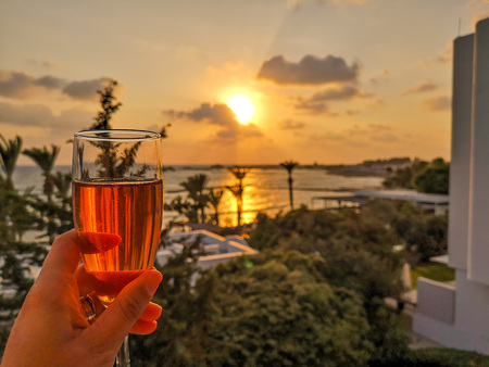 Woman holding a glass of ros? sparkling wine overlooking the bay of Paphos in Cyprus during sunset