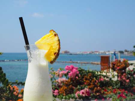 Glass with fresh pina colada cocktail with in the back the bay and castle of Paphos, Cyprus