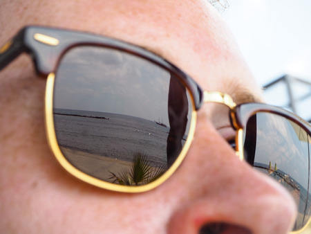 Mediterranean coast with passing ship reflected in male sunglasses