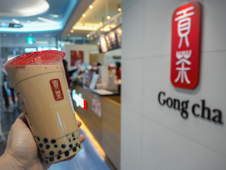March 2019 - South Korea: Caucasian female hand holding a jumbo size black milk tea with pearls or bubble tea from the Taiwanese brand Gong Cha Stock fotó - 127150636