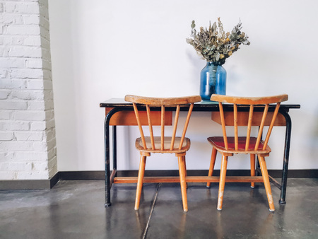 Vintage wooden elementary school desk and two wooden chairs with a dried flower arrangement in a blue vase against a white wall