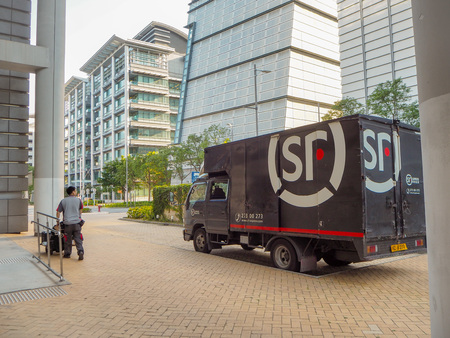 December 2018 - Hong Kong: Small truck and mail man from SF Express, China's second largest express courier company based in Shenzhen Stock fotó - 127150657
