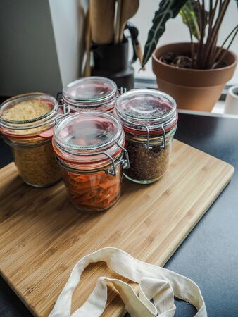 Four glass jars filled with dry food ingredients such as gluten free red lentil pasta and black lentils in a wooden cutting board Stock fotó - 131909935