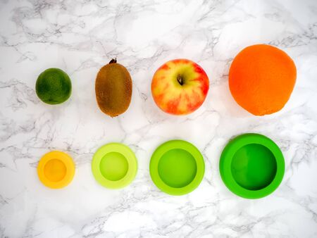 Variety of fruits and colorful ecological silicone food wraps for preserving cut foods for a zero waste lifestyle Stock fotó - 131910209