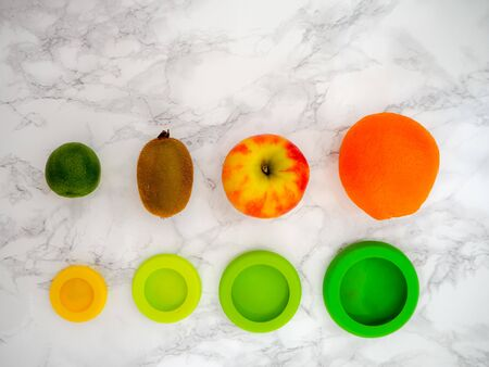 Variety of fruits and colorful ecological silicone food wraps for preserving cut foods for a zero waste lifestyle Stock fotó - 131909950