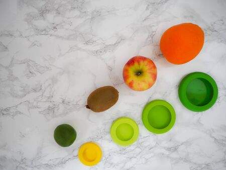 Variety of fruits and colorful ecological silicone food wraps for preserving cut foods for a zero waste lifestyle Stock fotó - 131909473