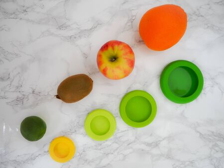 Variety of fruits and colorful ecological silicone food wraps for preserving cut foods for a zero waste lifestyle