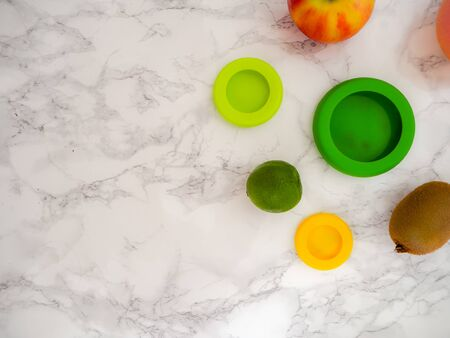 Variety of fruits and colorful ecological silicone food wraps for preserving cut foods for a zero waste lifestyle Stock fotó - 131909625