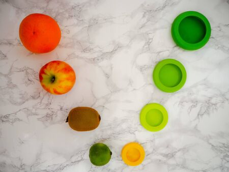 Variety of fruits and colorful ecological silicone food wraps for preserving cut foods for a zero waste lifestyle Stock fotó - 131910288