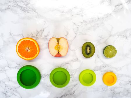 Variety of cut fruits and colorful reusable silicone food wraps for reducing food waste in a zero waste lifestyle Stock fotó - 131910638