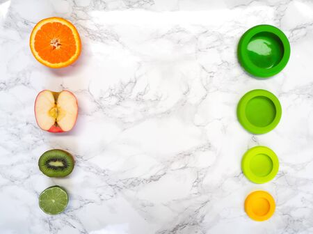 Variety of cut fruits and colorful reusable silicone food wraps for reducing food waste in a zero waste lifestyle Stock fotó - 131910168