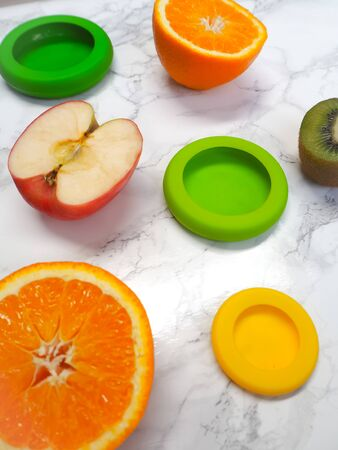 Variety of cut fruits and colorful reusable silicone food wraps for reducing food waste in a zero waste lifestyle Stock fotó - 131910152