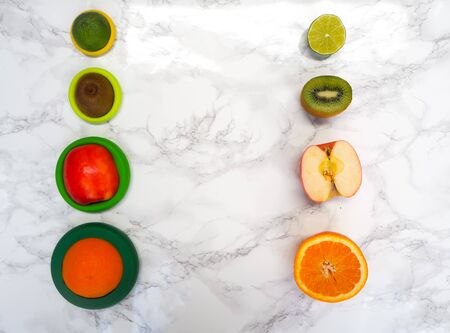 Sliced fruits in colorful reusable silicone food wraps for reducing food waste and food loss in a zero waste lifestyle