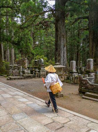 Pilgrim walking on the long path in the Okunion cemetery towards the Kobo Daishi mausoleum, birthplace of Shingon buddhism, in the UNesco site Koyasan, Japan Sajtókép