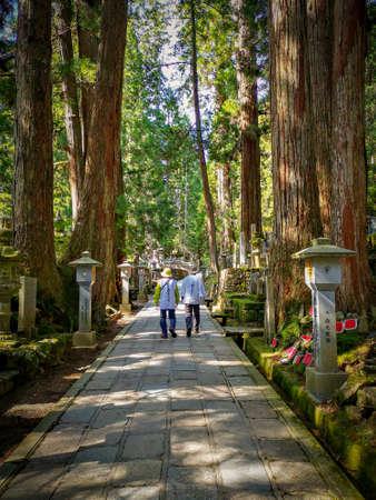 Pilgrims walking the long path in the Okunion cemetery towards the Kobo Daishi mausoleum, in the Unesco Wolrd Heritage Site Koyasan in Kansai, Japan Sajtókép