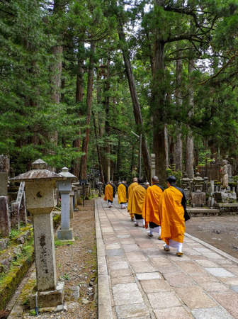 Monks walking on the 2 km long path with ancient tombs in the Okunoin cemetery towards the mausoleum of Kobo Daishi in the Unesco site Koyasan, Japan