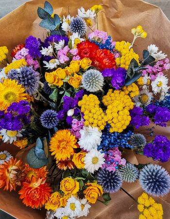 Vibrant dried flower arrangement in purple and yellow tones