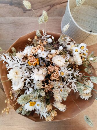 Dried flower arrangement for a wedding in neutral soft beige and white tones on a wooden background