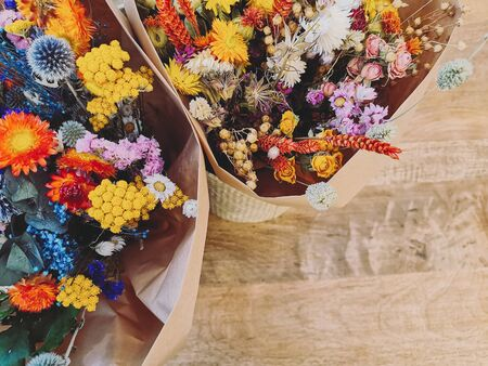 Vibrant dried flower arrangement in red, yellow and purples on a wooden background