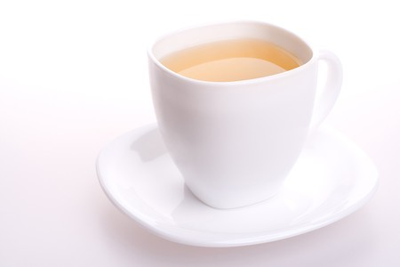 a white cup of tea standing on the table