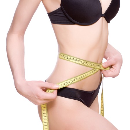 woman measuring waist: beautiful woman in lingerie measuring her waist