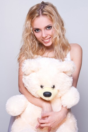 beautiful girl with a teddy bear on a gray background photo