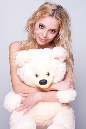 beautiful girl with a teddy bear on a gray background Stock Photo